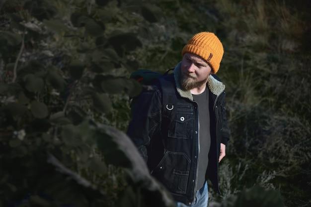 Portret van een jonge lamber wandelende man in het bos in de herfst en wegkijken. concept van mensen die in de natuur reizen.
