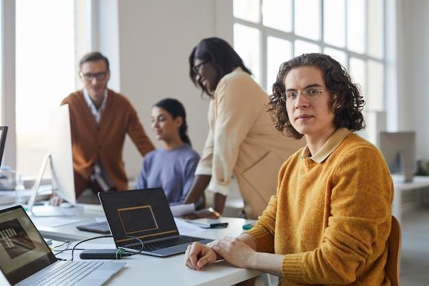Portret van een jonge langharige man die naar de camera kijkt terwijl hij een laptop op kantoor gebruikt met een divers team van softwareontwikkelaars, kopieer ruimte