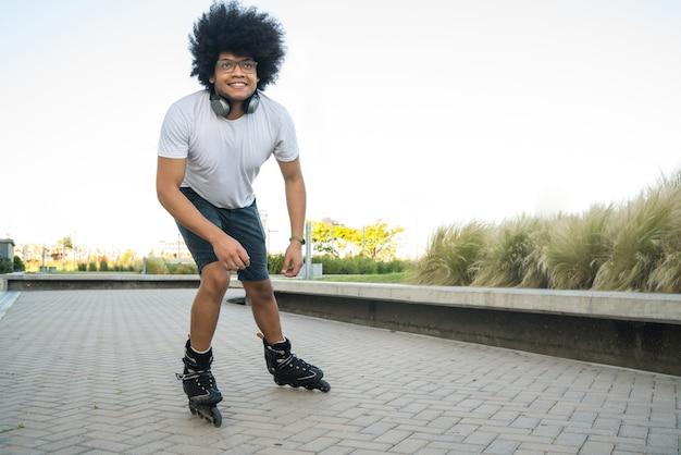 Portret van een jonge latijns-man die buiten op straat rolschaatst
