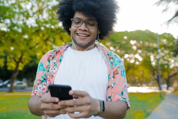 Portret van een jonge latijns-man die zijn mobiele telefoon gebruikt terwijl hij buiten op straat staat. stedelijk concept
