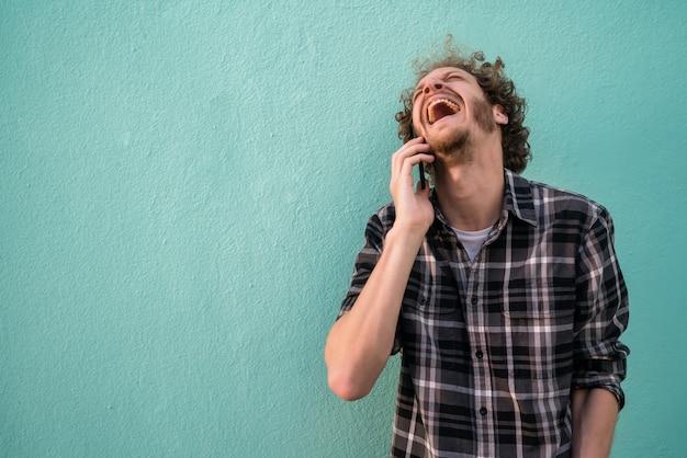 Portret van een jonge latijns-man lachen en praten aan de telefoon tegen lichtblauwe ruimte. communicatie concept.