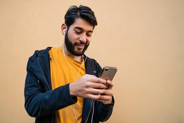 Portret van een jonge latijns-man met behulp van zijn mobiele telefoon met koptelefoon tegen gele ruimte. communicatie concept.