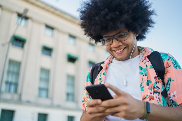 Portret van een jonge latijns-man met behulp van zijn mobiele telefoon terwijl hij buiten op straat staat