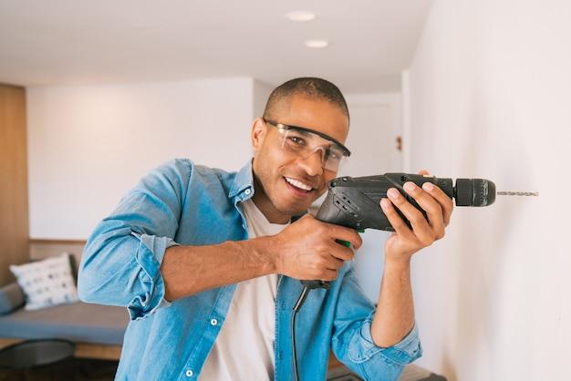 Portret van een jonge latijns-man met een elektrische boor en het maken van gat in de muur. interieurontwerp en huisrenovatieconcept.