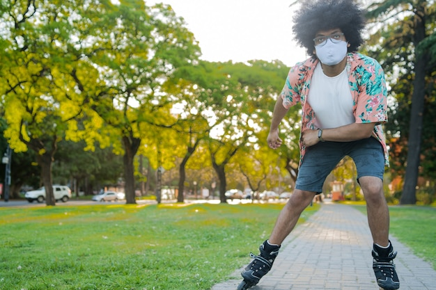 Portret van een jonge latijns-man met een gezichtsmasker terwijl hij buiten op straat rolschaatst