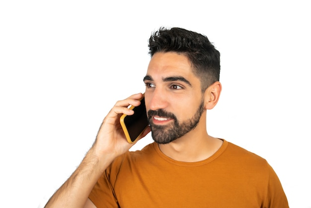 Portret van een jonge latijns-man praten aan de telefoon tegen witte achtergrond. communicatie concept.