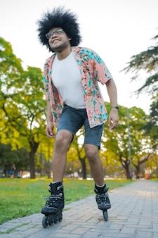 Portret van een jonge latijnse man die geniet terwijl hij buiten op straat rolschaatst