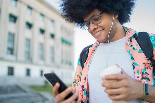 Portret van een jonge latijnse man die zijn mobiele telefoon gebruikt en een kopje koffie vasthoudt terwijl hij buiten op straat loopt. stedelijk concept