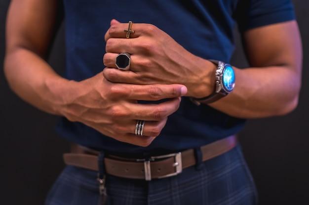 Portret van een jonge latino man op een zwarte muur. blauw poloshirt en geruite broek