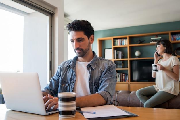 Portret van een jonge man aan het werk met een laptop vanuit huis terwijl vrouw praten over de telefoon op de achtergrond