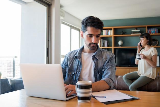 Portret van een jonge man aan het werk met een laptop vanuit huis terwijl vrouw praten over de telefoon