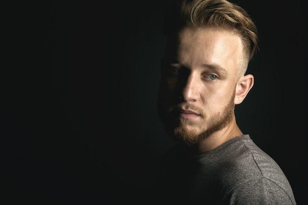 Portret van een jonge man boven zwarte achtergrond