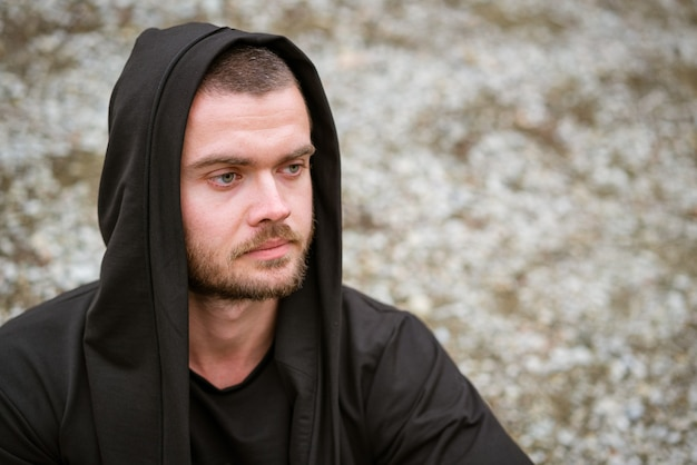 Portret van een jonge man buiten met een ongeschoren gezicht in een donkere trui met een capuchon op een natuurlijke rug...