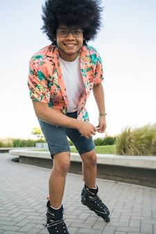 Portret van een jonge man camera kijken tijdens het rolschaatsen buiten op straat