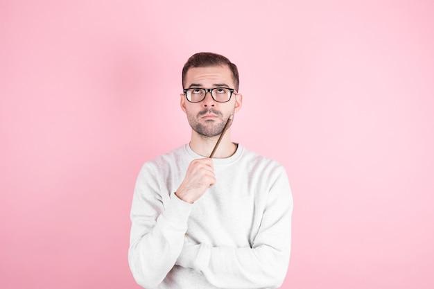 Portret van een jonge man denken met potlood tegen haar hoofd en kijkt naar de zijkant