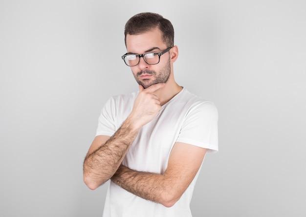 Portret van een jonge man denken met zijn hand aan zijn gezicht en kijkt naar de camera