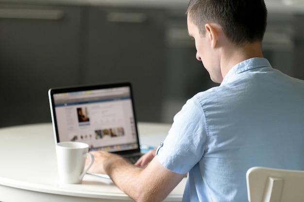 Portret van een jonge man die aan bureau werkt met laptop
