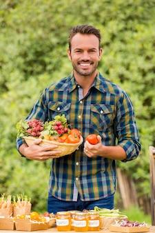 Portret van een jonge man die biologische groenten verkoopt