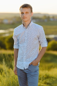 Portret van een jonge man die buitenshuis tijdens zonnige zomerdag