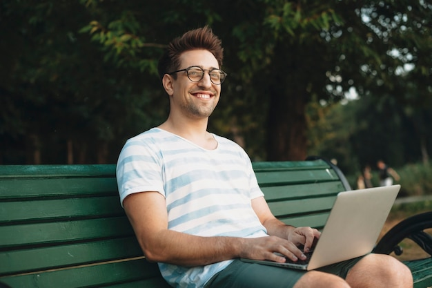 Portret van een jonge man die camera bekijkt die lacht terwijl hij een laptop op zijn benen buiten in het park houdt.