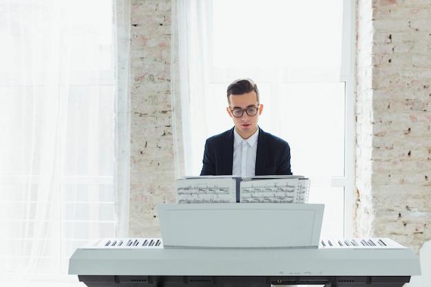 Portret van een jonge man die de pianozitting voor venster speelt