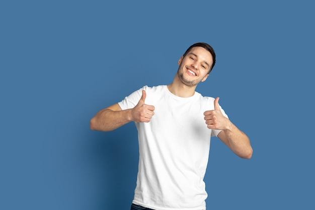 Portret van een jonge man die duimen opgeeft geïsoleerd op blauwe studio wall