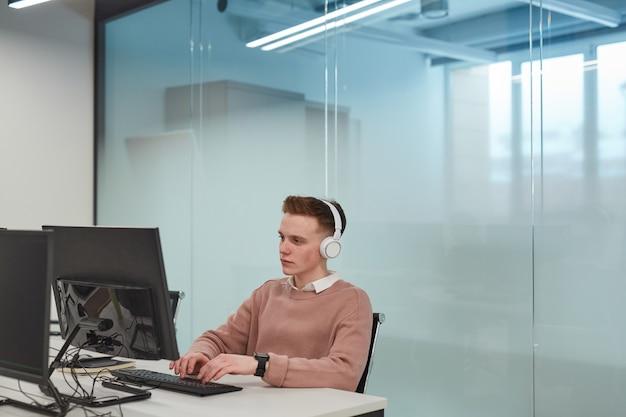 Portret van een jonge man die een computer gebruikt terwijl hij in een it-lab of kantoor werkt en een koptelefoon draagt, kopieer ruimte