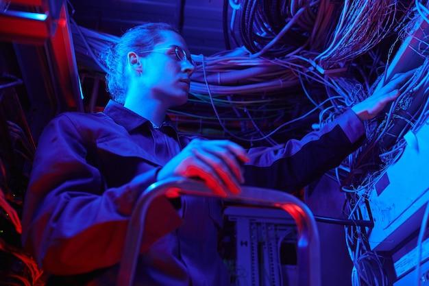 Portret van een jonge man die een computernetwerk opzet in de serverruimte met kabels en draden, kopieer ruimte