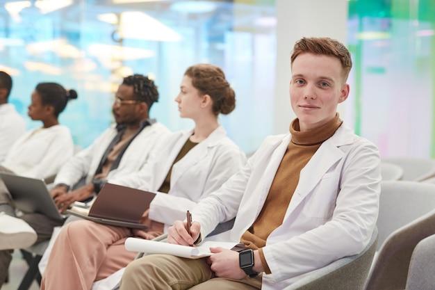 Portret van een jonge man die een laboratoriumjas draagt en naar de camera glimlacht terwijl hij in de rij zit met een multi-etnische groep mensen in het publiek tijdens een medisch seminar, kopieer ruimte