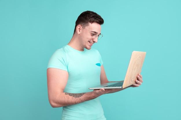 Portret van een jonge man die een laptop gebruikt die op de muur van de aquamarijnstudio wordt geïsoleerd