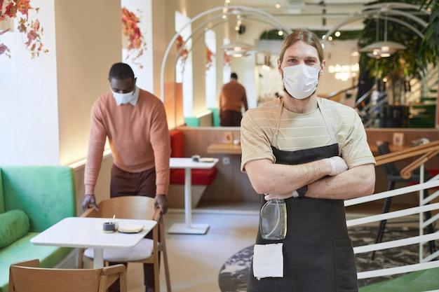 Portret van een jonge man die een masker draagt en naar de camera kijkt terwijl hij poseert met gekruiste armen in het café-interieur en ontsmettingsmiddelen vasthoudt, kopieer ruimte