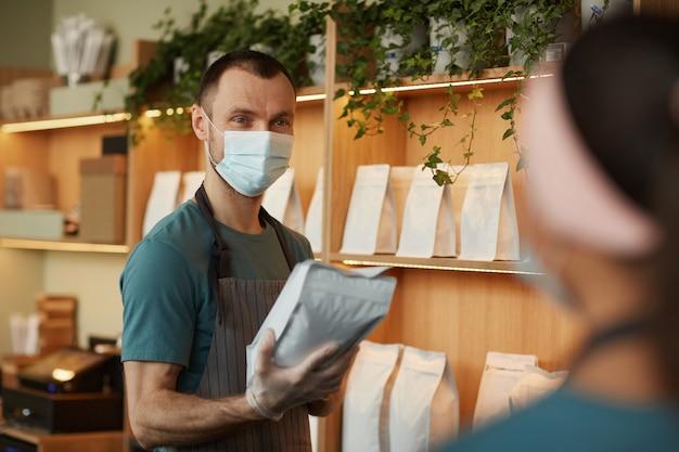 Portret van een jonge man die een masker draagt terwijl hij de klant bedient aan de toog in een café of coffeeshop, kopieer ruimte