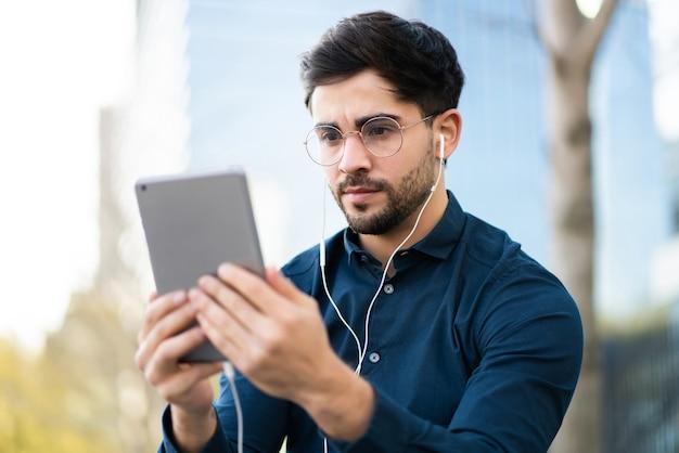 Portret van een jonge man die een videogesprek voert op een digitale tablet terwijl hij buiten staat