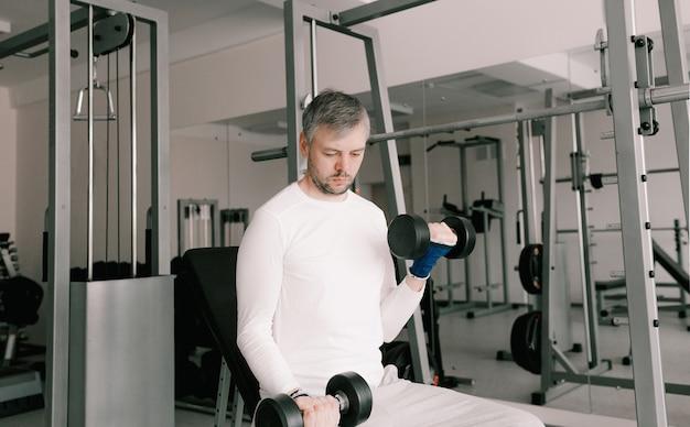 Portret van een jonge man die fysieke oefeningen doet, biceps training met halters in de sportschool, een kopie van de ruimte. in een wit t-shirt.