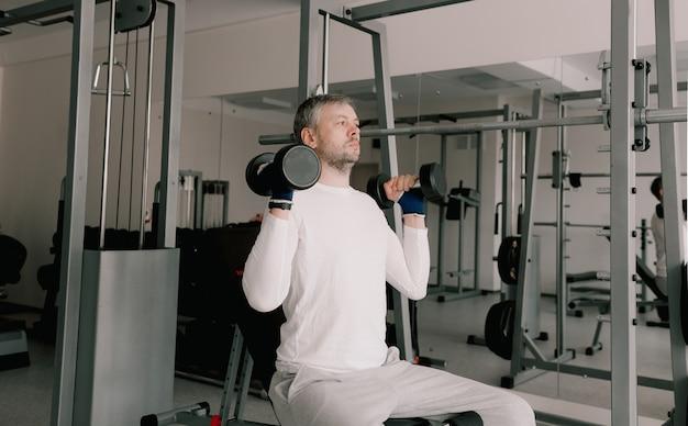 Portret van een jonge man die fysieke oefeningen doet, training met halters zittend op een bankje in de sportschool. in een wit t-shirt. gezonde levensstijl