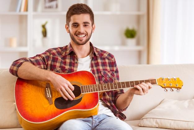 Portret van een jonge man die gitaar speelt thuis.