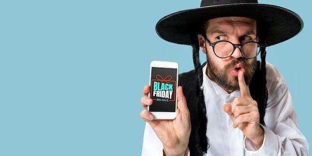 Portret van een jonge man die het smartphonescherm op een blauwe achtergrond toont. een geheim fluisteren. concept van verkoop, zwarte vrijdag, cybermaandag, financiën, zaken. online winkels en betalingen factuur.
