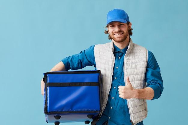 Portret van een jonge man die in de bezorgdienst werkt die hij naar de camera glimlacht en zijn duim tegen de blauwe achtergrond toont