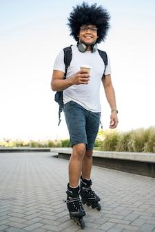 Portret van een jonge man die koffie drinkt terwijl hij buiten met skate-rollen staat