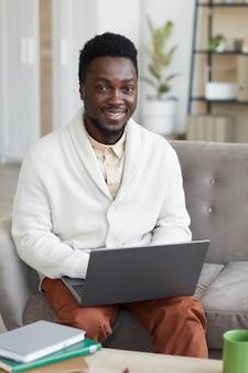 Portret van een jonge man die lacht aan de voorkant terwijl hij op de bank zit en op laptop werkt