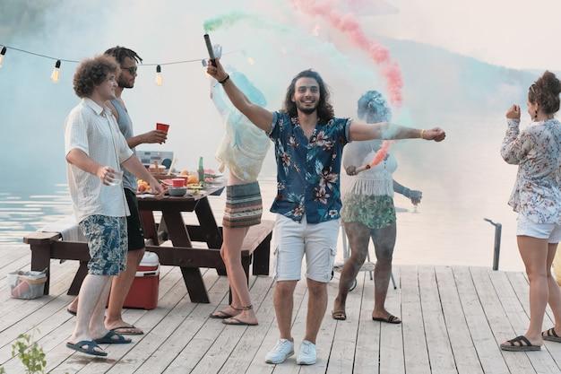 Portret van een jonge man die lacht naar de camera terwijl hij op een pier staat en danst tussen zijn vrienden