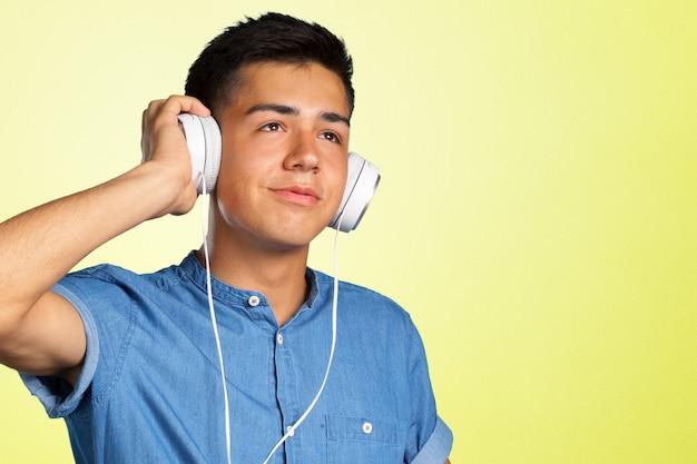 Portret van een jonge man die luistert naar muziek met een koptelefoon