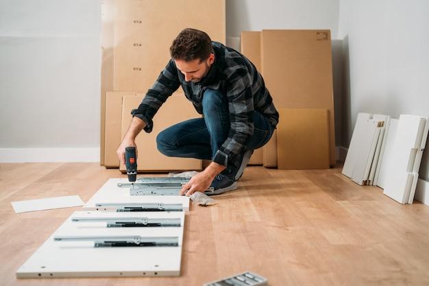 Portret van een jonge man die meubels monteert. doe het zelf meubelmontage.