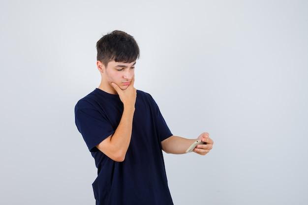 Portret van een jonge man die mobiele telefoon bekijkt, hand op kin in zwart t-shirt houdt en doordacht vooraanzicht kijkt