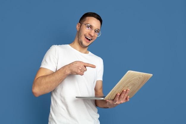 Portret van een jonge man die naar een laptop wijst die op een blauwe studiomuur is geïsoleerd