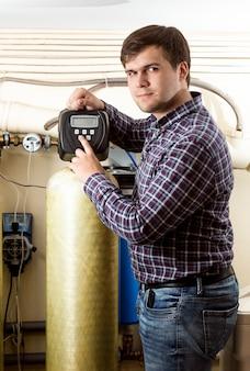 Portret van een jonge man die op de knop drukt op het bedieningspaneel van industriële apparatuur