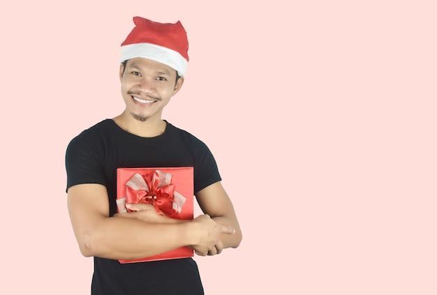 Portret van een jonge man die rode geschenkdoos knuffelt op rode achtergrond