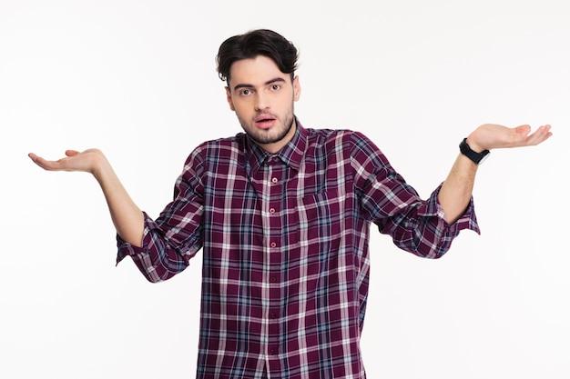 Portret van een jonge man die schouders ophaalt of copyspace op de handpalmen houdt geïsoleerd op een witte muur