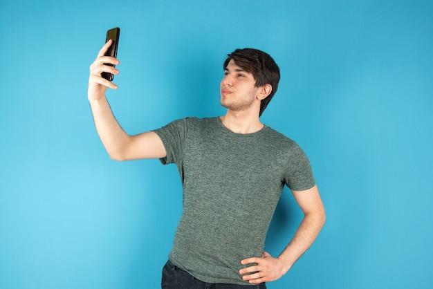 Portret van een jonge man die selfie met mobiele telefoon neemt tegen blauw.