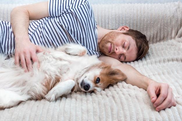 Portret van een jonge man die slaapt met zijn hond in een omhelzing op het bed